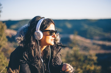 pretty and attractive girl with sunglasses and headphones on the mountain