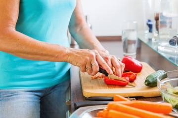 woman in the kitchen cutting red pepper