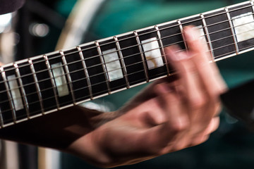 The musician's hand is blurred in motion on the fretboard on the strings of an electric guitar. Close-up.