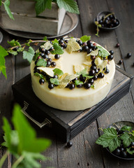 A modern mousse cake with a crusty nut layer, a layer of black wild currant and a mousse of white...