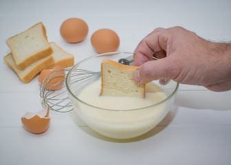 A man dips a piece of wheat bread in egg-milk mixture.