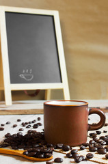 Coffee cup and coffee beans  on wooden background