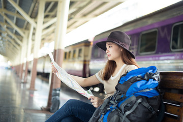 Young Asian woman tourist is looking at the map while traveling at the railway station.