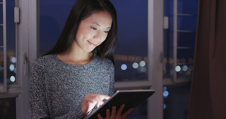 Woman watching on digital tablet at home