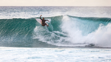 Surfing on the Banzai Pipeline wave break on Oahu North Shore in Hawaii, USA.