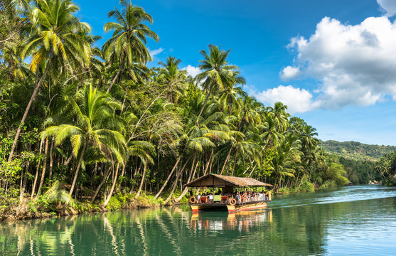 traditional raft boat with tourists on a jungle green river Loboc at Bohol island of Philippines