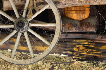 The old wooden wheel from the carriage hangs on the wall of the Ukrainian barn