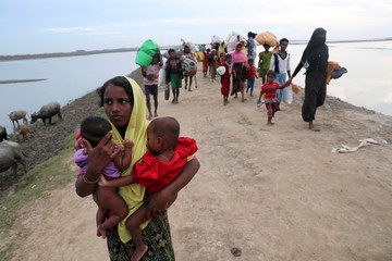 Fatema Khatun, 25, a Rohingya refugee women from Buthidaung, carries her children after crossing the Naf River with an improvised raft to reach to Bangladesh in Teknaf, Bangladesh