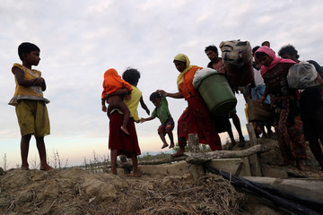 Rohingya refugees walk after crossing the Naf River with an improvised raft to reach to Bangladesh in Teknaf