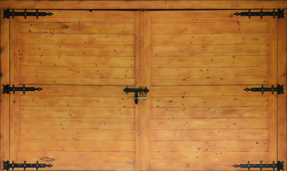 The texture of old wooden gates, old made of yellow treated wood with metal black door hinges