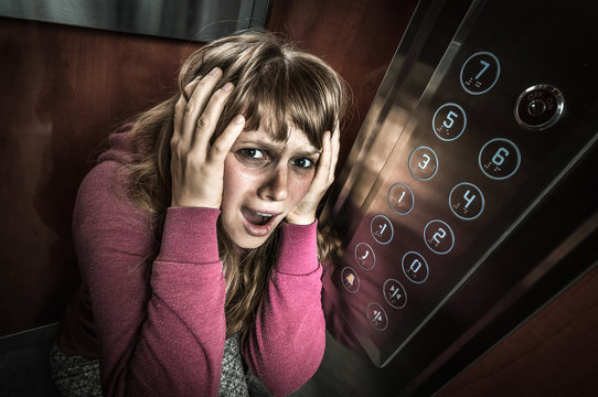 Shocked woman with claustrophobia in the moving elevator