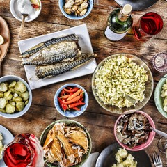 Dining table with a variety of snacks and salads. Salmon, olives, wine, vegetables, grilled fish toast. The concept of a family celebratory dinner. Thanksgiving, Christmas