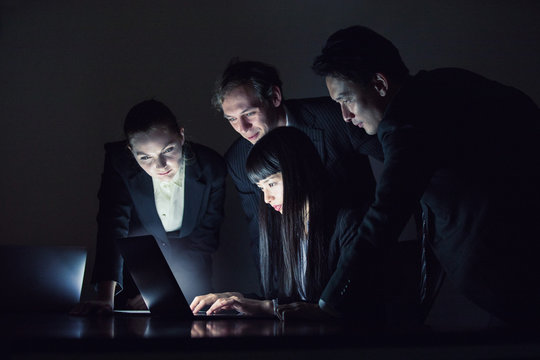 Group of people looking at screen of laptop PC.Group of people sitting on the floor and using mobile devices.
