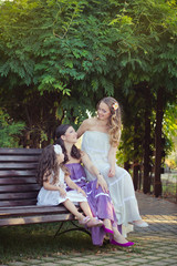 Adoring Brunette blond chestnut blue eyes sisters girls wearing cosy night white purple dress enjoying lifetime together summer sunny day in garden forest posing wooden bench happy smiling