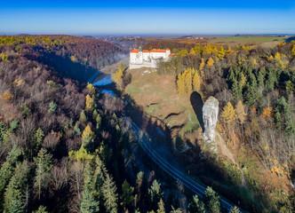 "Fototapeta Limestone monadnock, rock called ""Maczuga Herkuklesa"" (Hercules cudgel or bludgeon). Jurassic rock formation with Pieskowa Skala Castle in the background in Ojcow National Park near Krakow in Poland obraz"