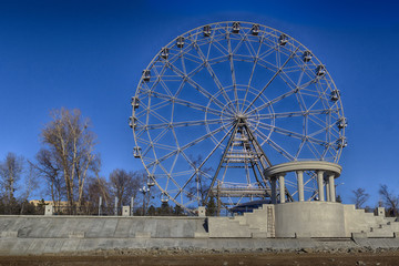 Ferris wheel in late autumn park on river or sea coast, together with ongoing repair or construction work in the park. Atmosphere of desolation and despondency. HDR image