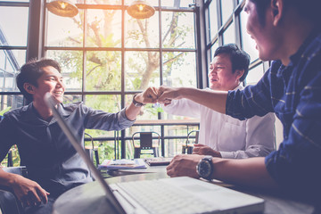 three Businessman giving fist bump for business meeting in cafeteria. Teamwork Concept