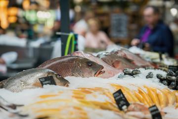 Sale of fresh frozen arranged fish on ice in farmer's bazaar. Open showcases of seafood market