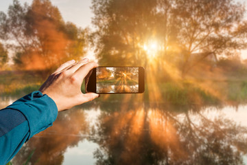 Photographing with smartphone in hand. Travel concept. Misty dawn on the river