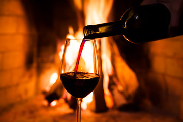 Bottle of wine and a glass against the fire
