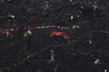 black concrete wall with stains of paint