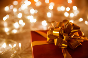 Present Gift Box with Bow Ribbon, Christmas Decoration over Defocused Night Lights Background