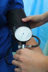 Nurse measures the blood pressure to the patient in the emergency room