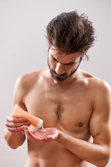 Young handsome man is applying skin cream.