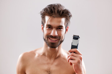 Young man is holding electric razor and he is going to shave his beard.