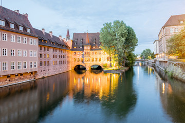 Night view on the water channel with beautiful illuminated buildings in Nurnberg city, Germany