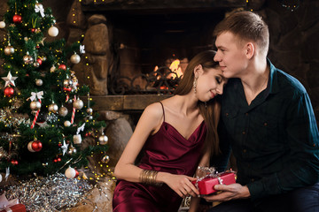 Young couple opening christmas gifts