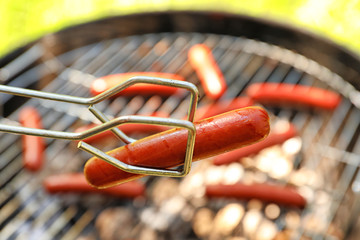 Tongs holding sausage near barbecue grill