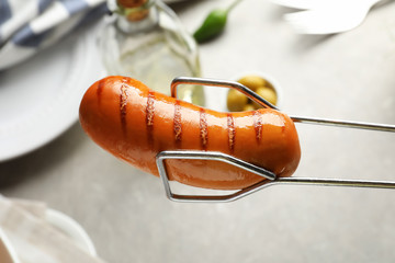 Tongs holding grilled sausage near dinner table