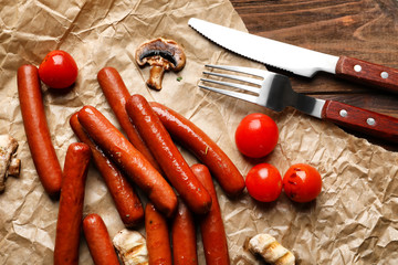 Grilled sausages, vegetables and utensils on baking paper