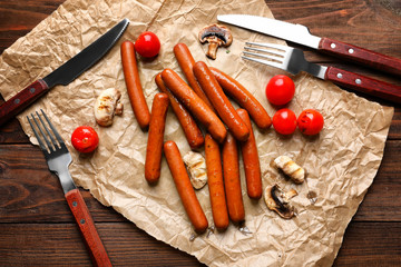 Composition with grilled sausages, vegetables and cutlery on kitchen table