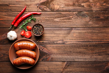 Composition with grilled sausages, pepper and vegetables on wooden background