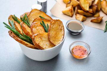 Bowl of tasty rosemary potatoes on table