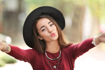 Attractive hipster girl taking selfie outdoors