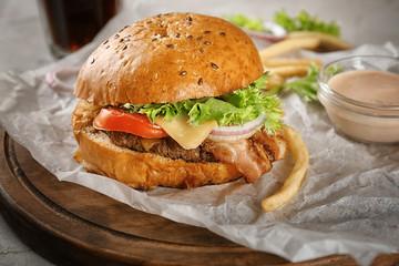 Tasty beef burger on wooden board