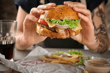 Woman holding tasty beef burger over table