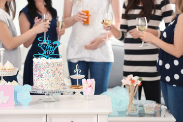 Tasty treats served for baby shower party on table and blurred women on background