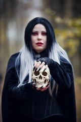 Photo of vampire girl in black cloak with skull in hands