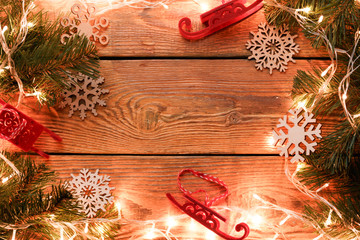 Picture on top of wooden surface with burning garland, branches of spruce, Christmas toys,