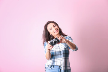 Beautiful female photographer with camera on color background