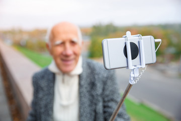 Close-up of a monopod with a telephone in the hands of an elderly man.