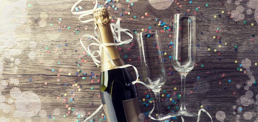 Picture of bottle of wine with two wine glasses, confetti