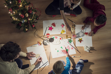 Top view of a family with two kids and a baby making Christmas decorations