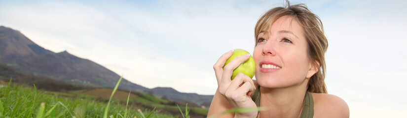 Beautiful woman eating a green apple in nature - banner template web