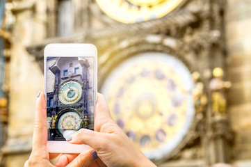 Tourist taking picture of a famous attraction with smartphone. Woman taking photo of the Prague astronomical clock in Czech Republic.