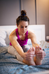 Sporty shape middle aged woman stretching yoga exercise while sitting forward on the bed while her hands are holding the feets.